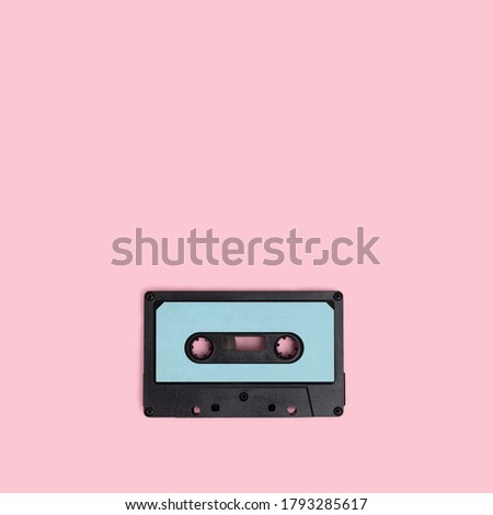 Cassette tape on a pink background. Minimal composion with copy space.