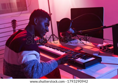 Professional african american musician recording synthesizer in digital studio at home, Music production technology concept. Royalty-Free Stock Photo #1793290942