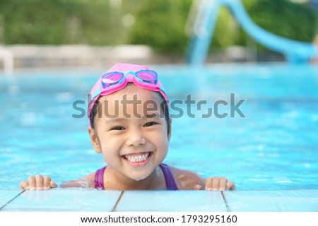 Asian child cute or kid girl wear swimming suit and goggles on swimming pool and smile with happy fun in water park for learn and training swim or refreshing and relax with exercise on summer holiday #1793295160