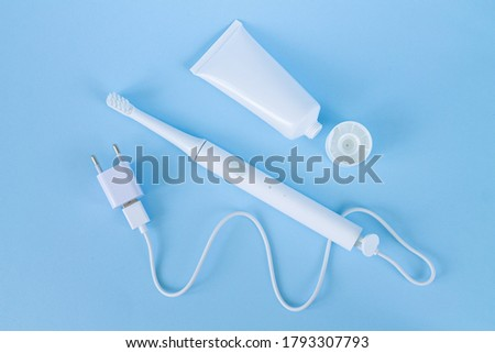 Rechargeable sonic or electric toothbrush set with charger and toothpaste on blue background top view