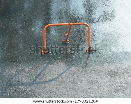 red parking lot barrier with padlock for private parking with a fence background in rain #1793321284