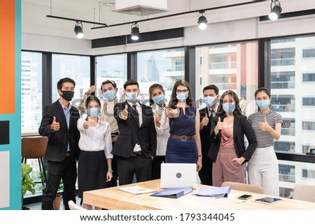 Multi-ethnic business group confident wearing face mask and showing thumbs up in new normal office at business district, While pandemic of virus Royalty-Free Stock Photo #1793344045
