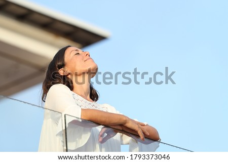 Relaxed adult woman breathing fresh air standing on a hotel balcony at summer Royalty-Free Stock Photo #1793373046