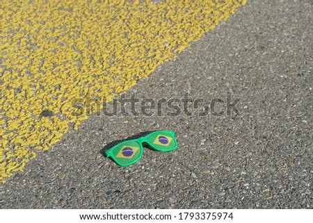 Kitschy broken sunglasses with printing applied color of Brazilian flag lying near yellow pedestrian crossing in Switzerland as a symbol of Carnival in Rio. #1793375974