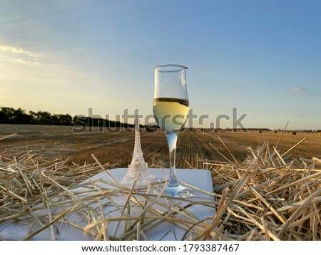 Haystacks at sunset. A glass of champagne stands on a white plastic board. Beautiful nature picture. A sense of peace and relaxation. The bright sun sets on the horizon. Sun's rays flood wheat field.