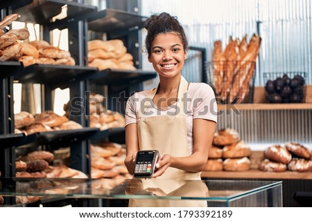 Young woman wearing apron assistant at friendly bakery shop small business standing holding card reader machine looking camera smiling friendly taking payment