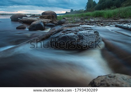 Blue mistycal night landscape with water stream in motion blur and stones in the coast. Northern Dvina river, Russia. #1793430289