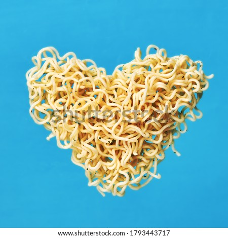 instant noodles. levitated noodle heart symbol over blue background. outer space. for design and ornate. fast food concept.