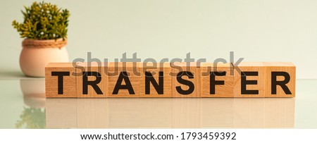 Transfer message word on a wooden desk on cube blocks with a flower on background. Transfer sign on a wooden table on brick background