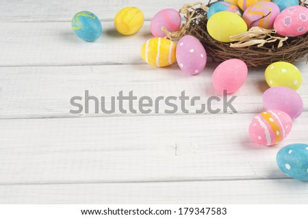 Colorful Easter Eggs in Nest from Top Side View on White or Gray Rustic Wood Background with room or space for copy, text, words