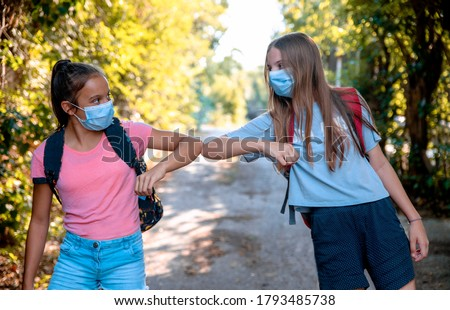 Two Teenage Girls say hello touching hands elbow meeting in the Park on the way to School. New handshake due to Coronavirus pandemic safety protective behavior Royalty-Free Stock Photo #1793485738