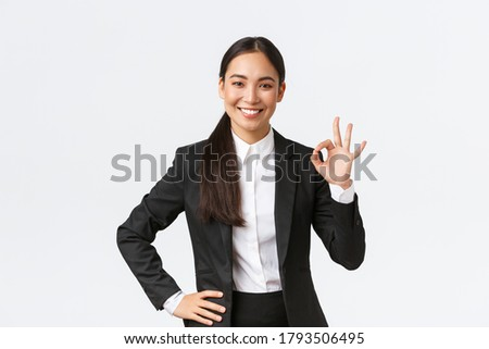 Professional female manager in black suit looking assertive, encourage everything okay, assure work done, showing okay gesture and smiling in approval, standing satisfied over white background #1793506495