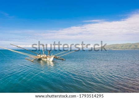 A fishing boat with outriggers anchored at Manga fish port, in Tagbilaran City, Bohol. The mountains of Maribojoc are in the background.