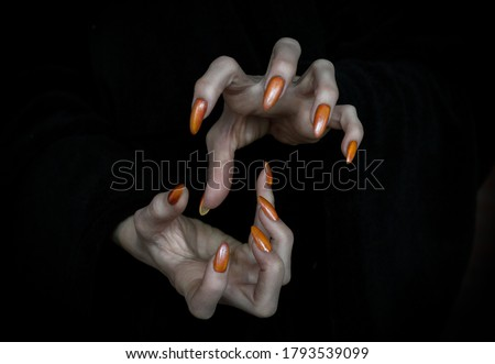 Witch hands with sharp nails and long pale fingers in the dark, low key, selected focus. Halloween, witchcraft, magic, evil, creepy and monster concept. Royalty-Free Stock Photo #1793539099