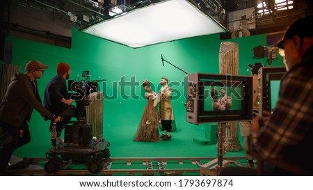 On Big Film Studio Professional Crew Shooting Period Costume Drama Movie. On Set: Director Controls Cameraman Shooting Green Screen Scene with Two Actors Talented Wearing Renaissance Clothes Talking Royalty-Free Stock Photo #1793697874
