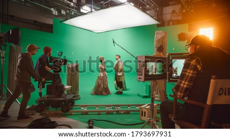 On Big Film Studio Professional Crew Shooting Period Costume Drama Movie. On Set: Director Controls Cameraman Shooting Green Screen Scene with Two Actors Talented Wearing Renaissance Clothes Talking
