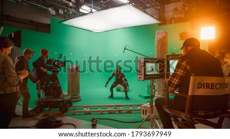 In the Big Film Studio Professional Crew Shooting Blockbuster Movie. Director Commands Cameraman to Start shooting Green Screen CGI Scene with Actor Wearing Motion Capture Suit and Head Rig Royalty-Free Stock Photo #1793697949