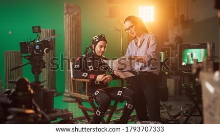 On Film Set: Prominent Female Director Explains Scene to Male Actor Wearing Motion Capture Suit and Playing Green Screen Scene in Superhero Movie. On Big Film Studio Professional Crew