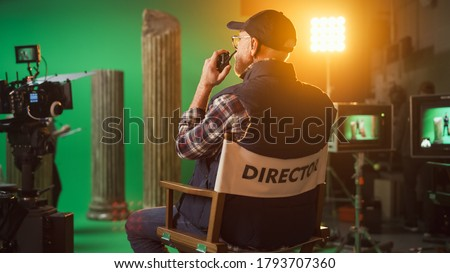 """Prominent Successful Senior Director is Sitting at His Chair and Commands """"Action!"""" to Start Shooting. On the Studio Film Set with High End Equipment Professional Crew Shooting High Budget Movie Royalty-Free Stock Photo #1793707360"""