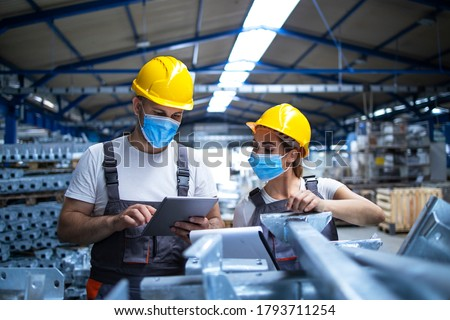 Industrial workers with face masks protected against corona virus discussing about production in factory. People working during COVID-19 pandemic. Royalty-Free Stock Photo #1793711254