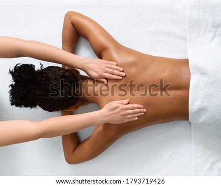 Slim black woman receiving full body massage at modern spa, top view #1793719426