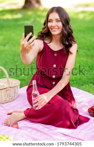 leisure and people concept - happy smiling woman with smartphone and fizzy drink in bottle sitting on picnic blanket and taking selfie at summer park