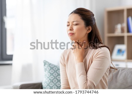 health, cold and people concept - sad sick young asian woman with sore throat at home Royalty-Free Stock Photo #1793744746