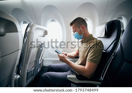 Man wearing face mask and using phone inside airplane during flight. Themes new normal, coronavirus and personal protection.  Royalty-Free Stock Photo #1793748499
