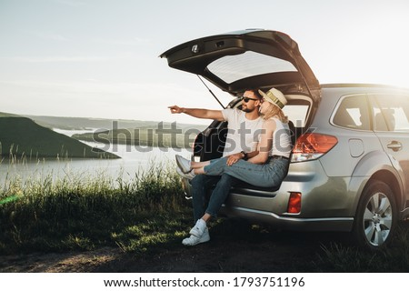 Man and Woman Relaxing Inside Car Trunk Enjoying Weekend Road Trip, Travel and Adventure Concept Royalty-Free Stock Photo #1793751196