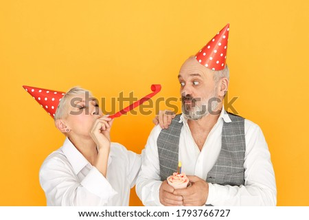Studio image of attractive cheerful mature woman blowing paper tube while having fun at birthday party standing next to her elderly bearded husband in cone hat, having shcoked look, holding cupcake