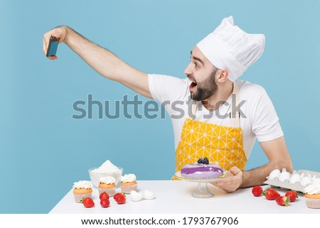 Excited young bearded male chef or cook baker man in apron white t-shirt toque chefs hat cooking at table isolated on blue background studio. Cooking food concept. Doing selfie shot on mobile phone