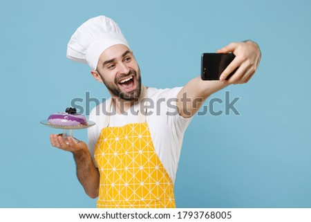 Excited young bearded male chef cook baker man in apron white t-shirt toque chefs hat isolated on blue background studio. Cooking food concept. Hold dessert cake doing selfie shot on mobile phone
