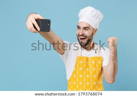 Joyful young bearded male chef or cook baker man in apron white t-shirt toque chefs hat isolated on blue wall background. Cooking food concept. Doing selfie shot on mobile phone, doing winner gesture