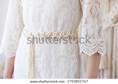 Handmade macrame dress belt. Natural cotton threads and wooden beads. Stylish decoration for women 's dress.  Macrame braiding and cotton threads. Female hobby.  Royalty-Free Stock Photo #1793801767