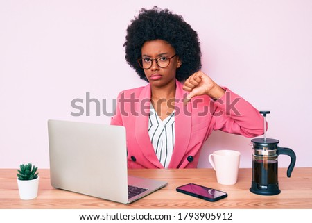 Young african american woman working at desk using computer laptop with angry face, negative sign showing dislike with thumbs down, rejection concept