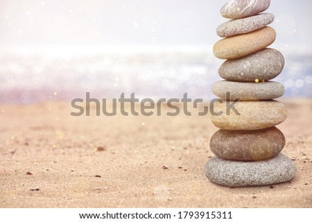 Pyramid stones balance on the sand of the beach.