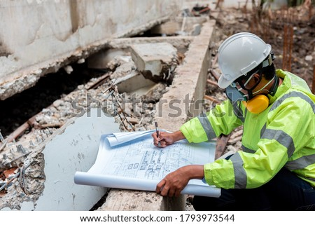 Civil Engineer People wearing face mask and safety helmet while looking to detail in drawing paper on construction site. Surveyor and checking in the Construction building for Demolishing and Renovate Royalty-Free Stock Photo #1793973544