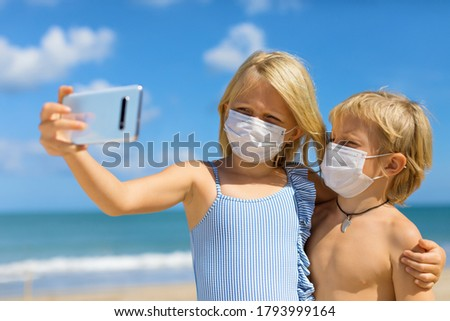 Funny kids taking selfie photo by smartphone on tropical sea beach. New rules to wear cloth face covering mask at public places due coronavirus COVID 19. Family holidays with children, summer travel.