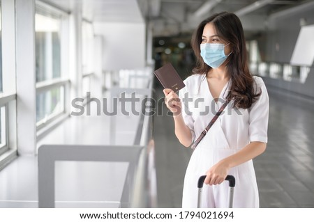 A traveller woman is wearing protective mask in International airport, travel under Covid-19 pandemic, safety travels, social distancing protocol, New normal travel concept . #1794021694