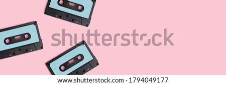Cassette tapes on a pink pastel background. Artistic banner with place for your design.