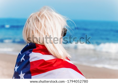 Caucasian blonde woman holding american flag leaning against back and looking at sea