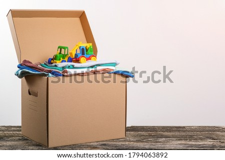 Donation box with children's things and toys. Donation box full with stuff for donate. Help poor. Case full of clothing for poor families.  Cardboard box with clothes for charity. Donation. #1794063892