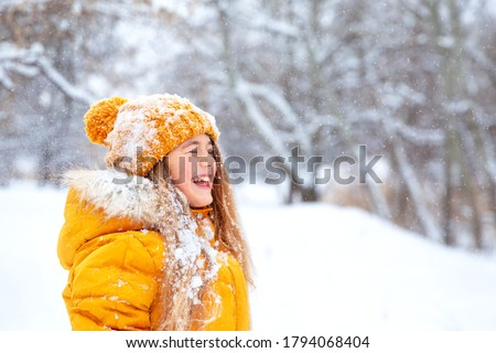 Outdoor close-up portrait of young beautiful happy smiling girl, wearing yellow jacket and knitted hat walking in winter park