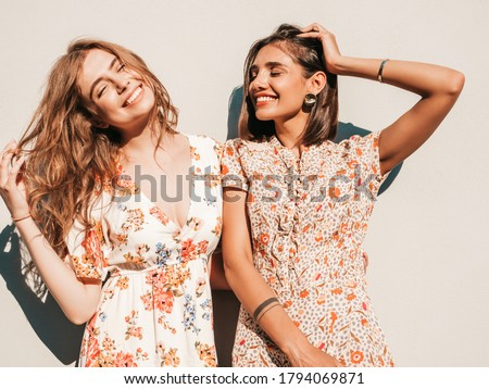 Two young beautiful smiling hipster girls in trendy summer sundress.Sexy carefree women posing near wall on the street background. Positive models having fun and hugging