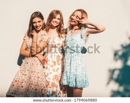 Three young beautiful smiling hipster girls in trendy summer sundress.Sexy carefree women posing on the street near wall. Positive models having fun and hugging #1794069880