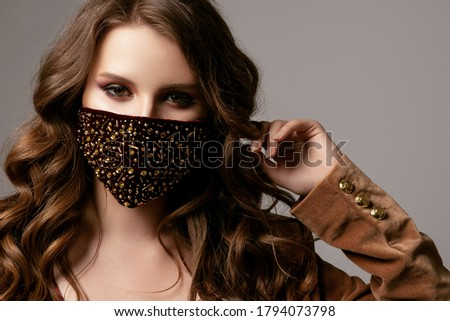 Woman wearing stylish protective dark red velvet face mask with golden rhinestones, beads. Fashion accessory during quarantine of coronavirus. Close up studio portrait