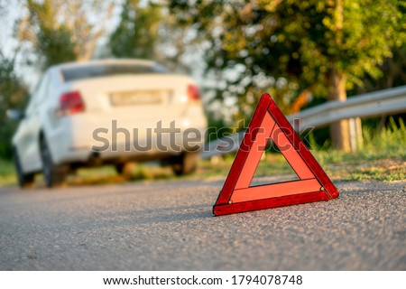 red triangle sign on the road as the symbol of the car crash accident on highway
