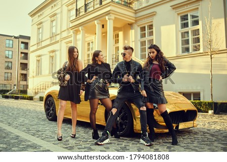 A wealthy man in a golden car surrounded by women. The man is all in gold, is popular with girls. Friends came to a party at the cottage. A man surrounds women. Royalty-Free Stock Photo #1794081808