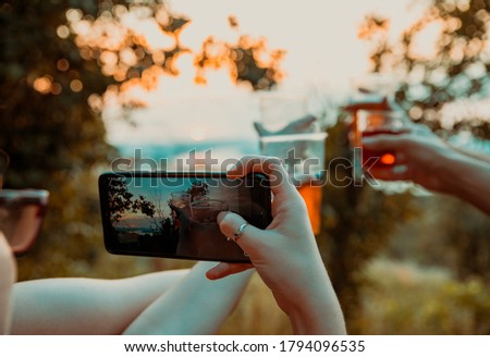 Girl using Smart phone to take a picture of Beer in big Glasses. Photographing friend hands holding beer for Toast in Picnic or festival Outdoors