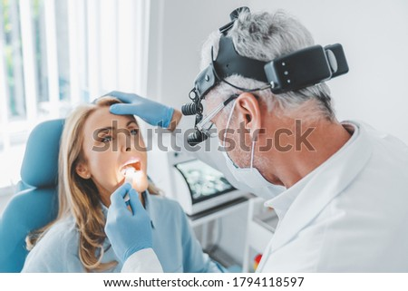 Mature doctor checking woman throat with medical stick Royalty-Free Stock Photo #1794118597